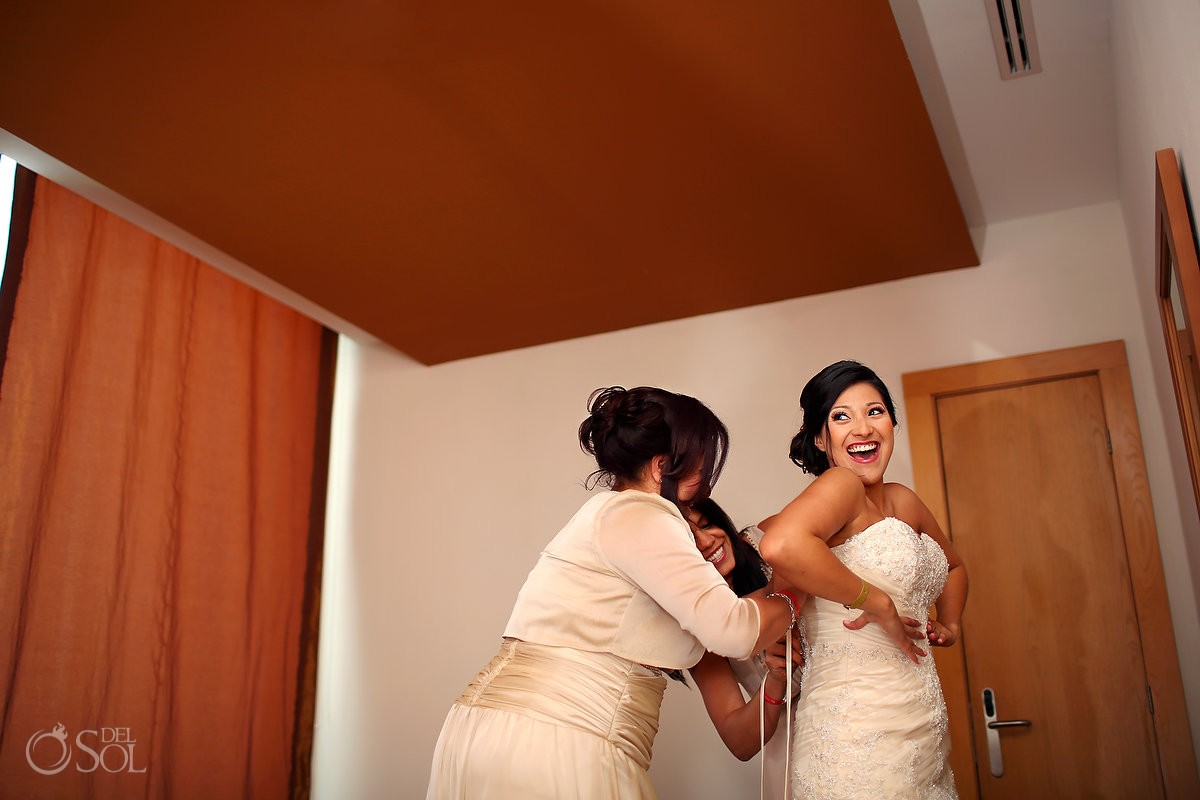 Riviera Maya bride putting on bridal gown