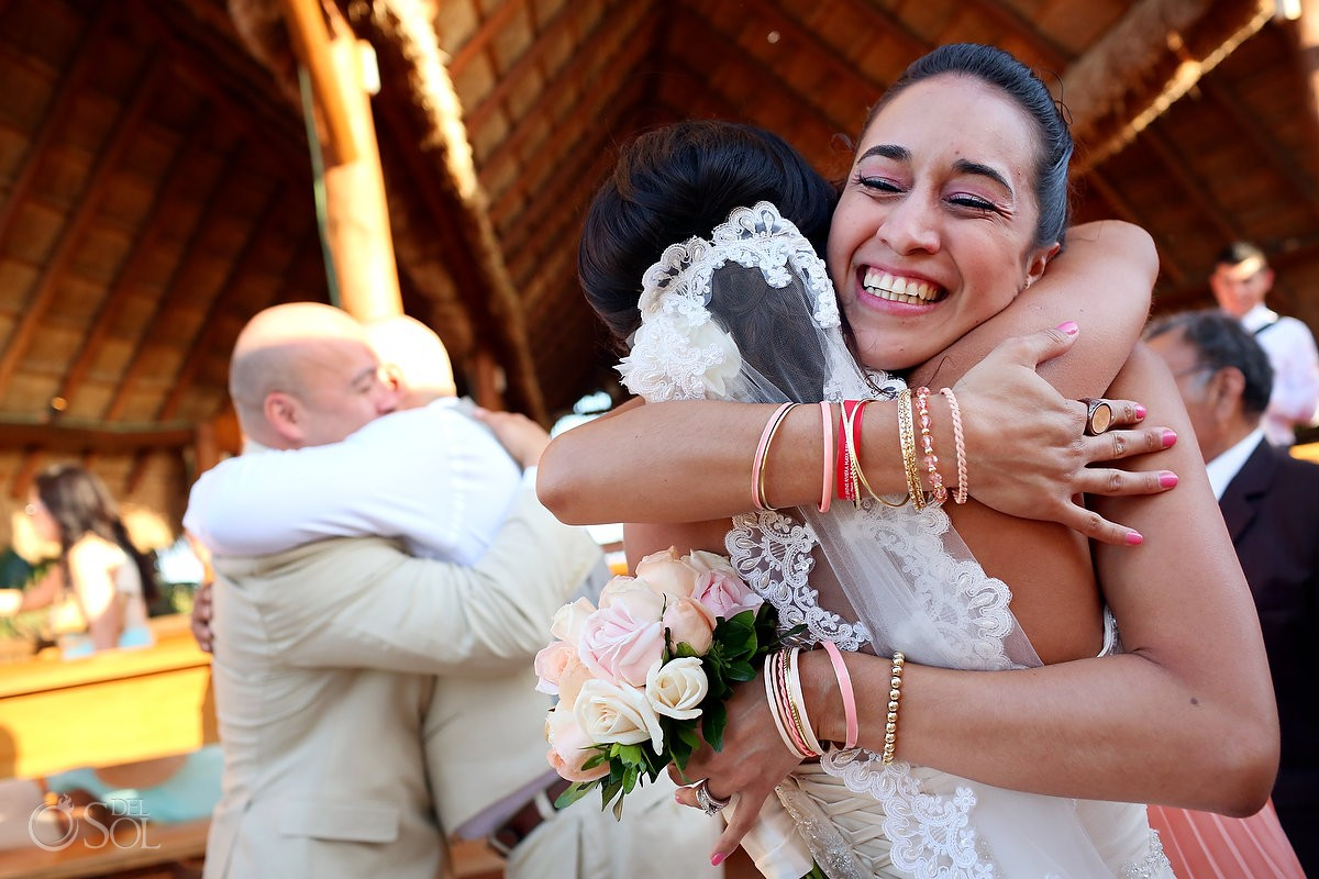 Guest hugging bride destination wedding palapa