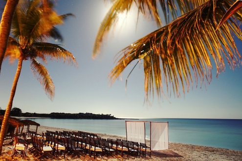 Hotel Esencia weddings beach ceremony location with chairs under full moonlight