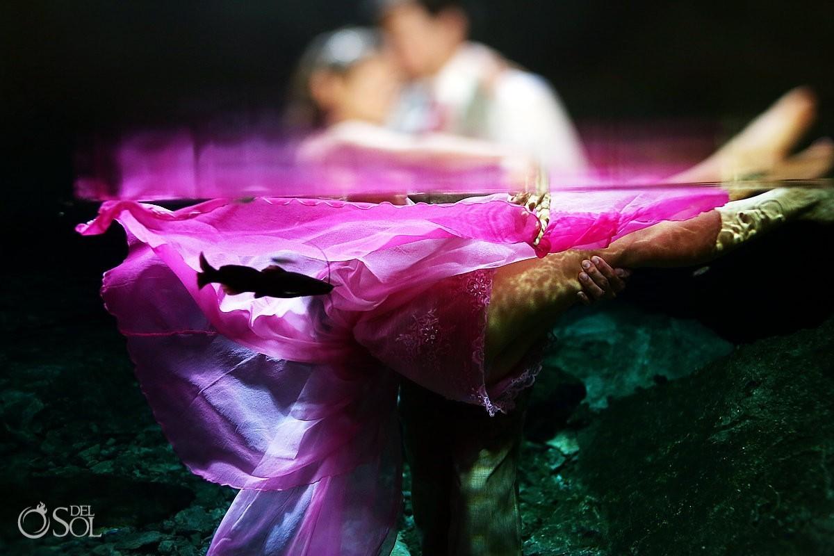 Fish swim by bride underwater trash the dress cenote