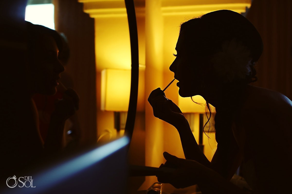 Bride applying makeup in yellow light silhouette