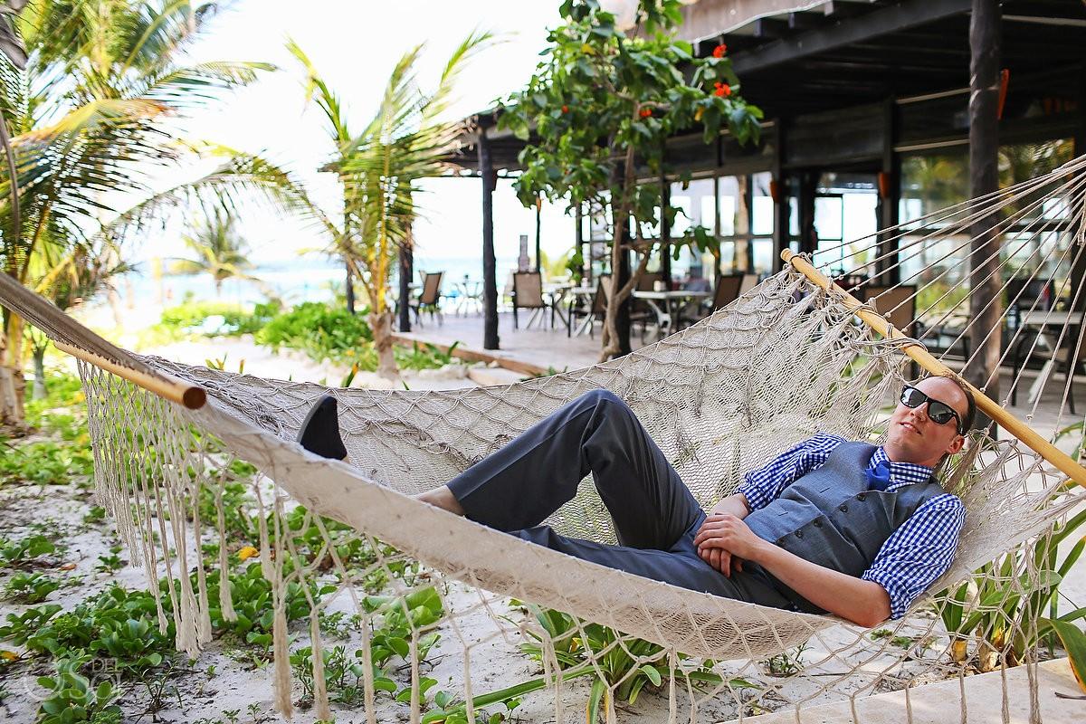 tulum #Destinationwedding groom chilling in a hammock in front of the Caribbean ocean