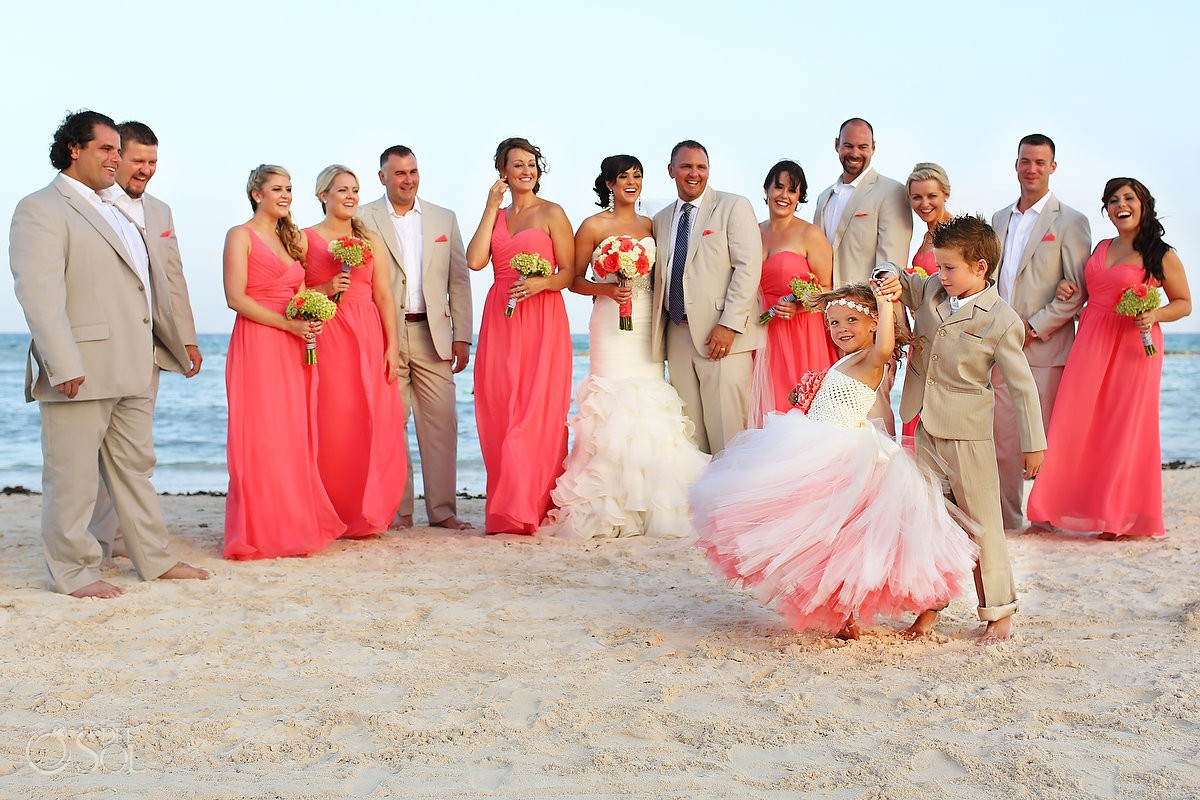 bridal party with cute ring bearer dancing with flower girl twirling pink colors