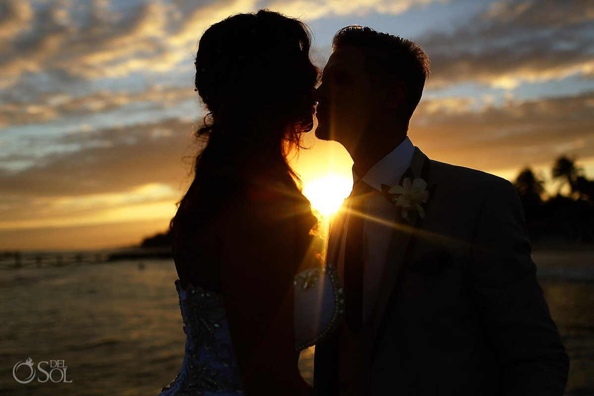 Destination wedding photograph of bride and groom kissing at hotel in mexico