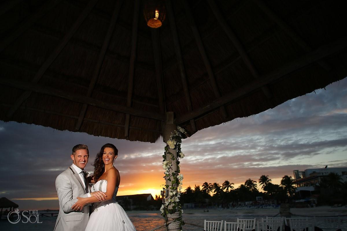 Bride and groom kiss at sunset at viceroy hotel riviera maya