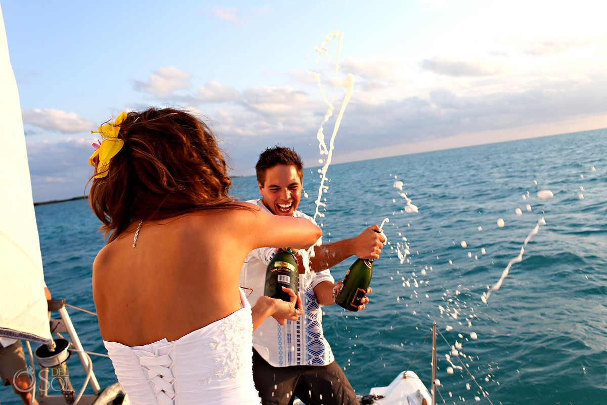 Bride and groom spraying champagne on each other on a sailboat in Ambergris Caye, Belize