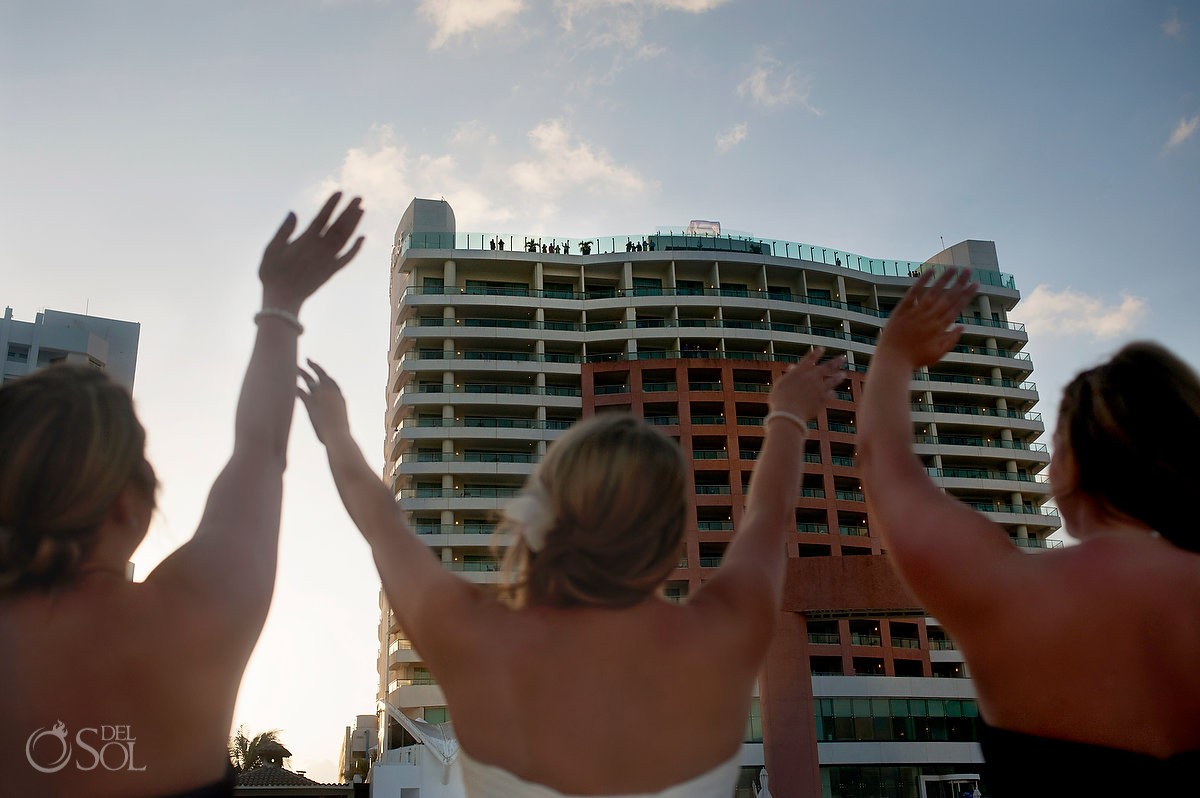 destination wedding photo bride waving at guests at beach palace cauncun