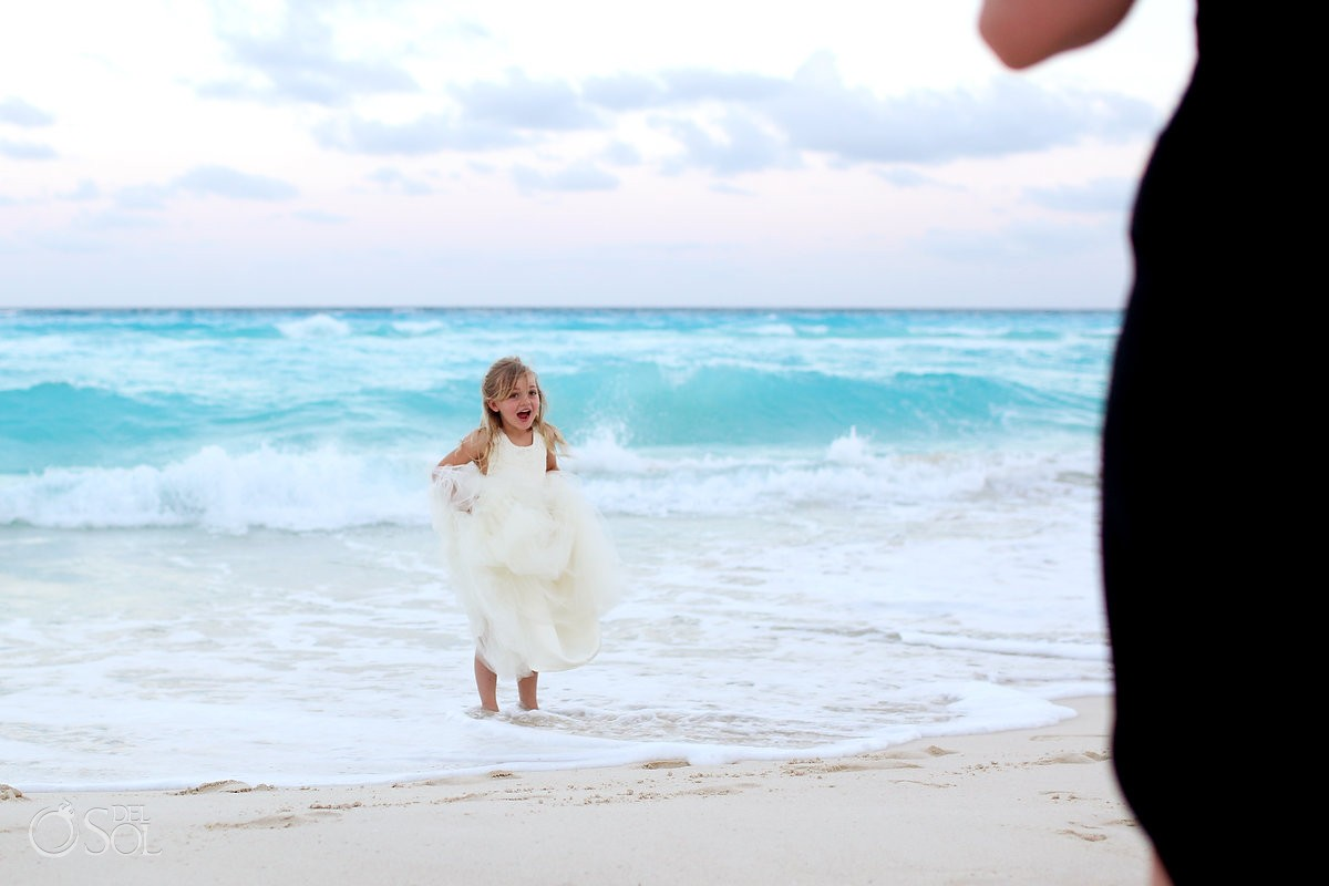 cute flower girl jumping in the ocean at beach palace hotel cancun
