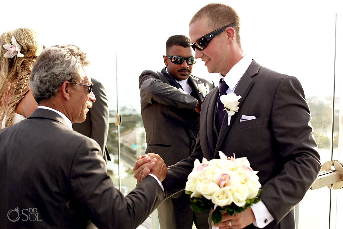 Father shakes hands with groom during his wedding at beach palace cancun