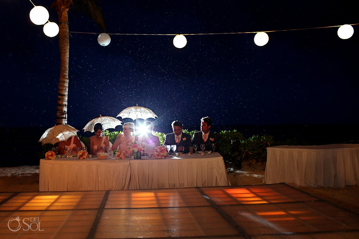 Bride and groom sitting at table under the rain at Blue Bay Grand Esmeralda