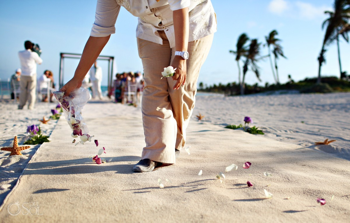 wedding coordinator spreading rose petals in the aisle at dreams tulum hotel for destination weddings