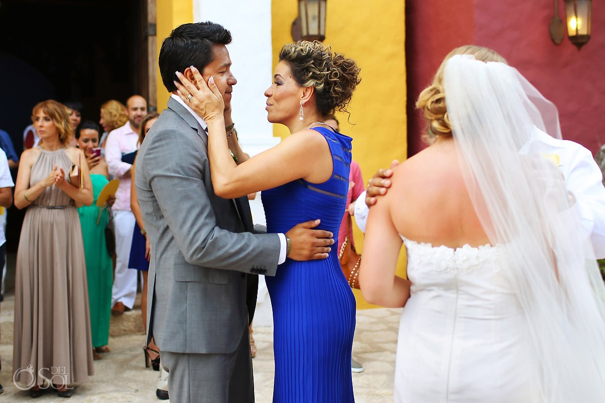 Mother embraces her son's face at his Xcaret Park destination wedding in Mexico