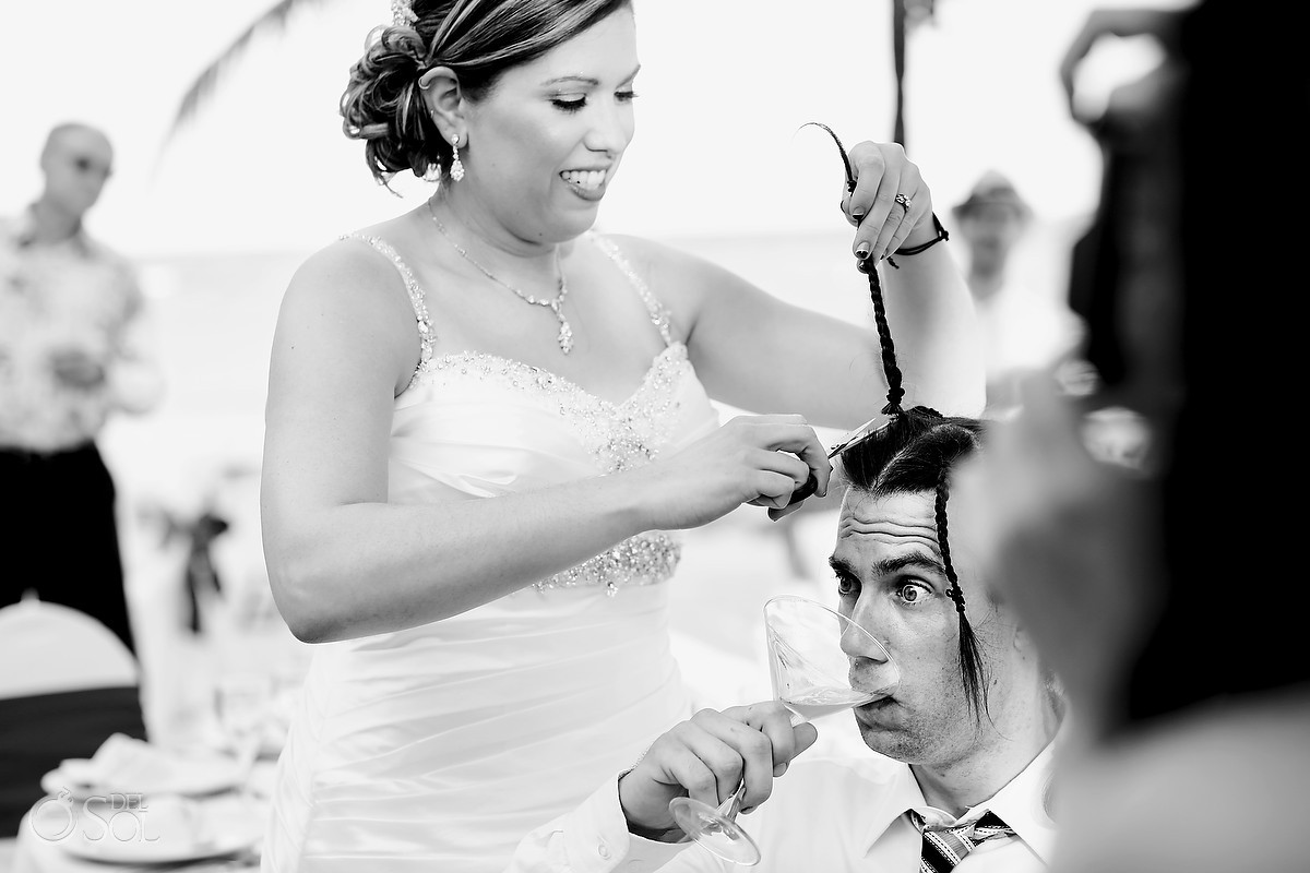 bride is cutting grooms hair while he drinks martini
