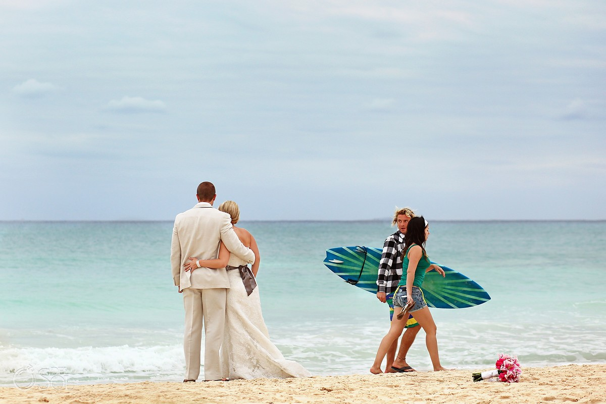 surfer walks past bride and groom in playa del carmen mexico