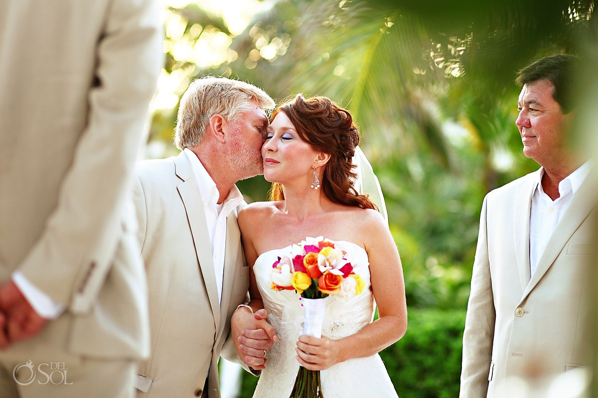 father kisses his daughter goodby as she is walking the aisle for a destination wedding