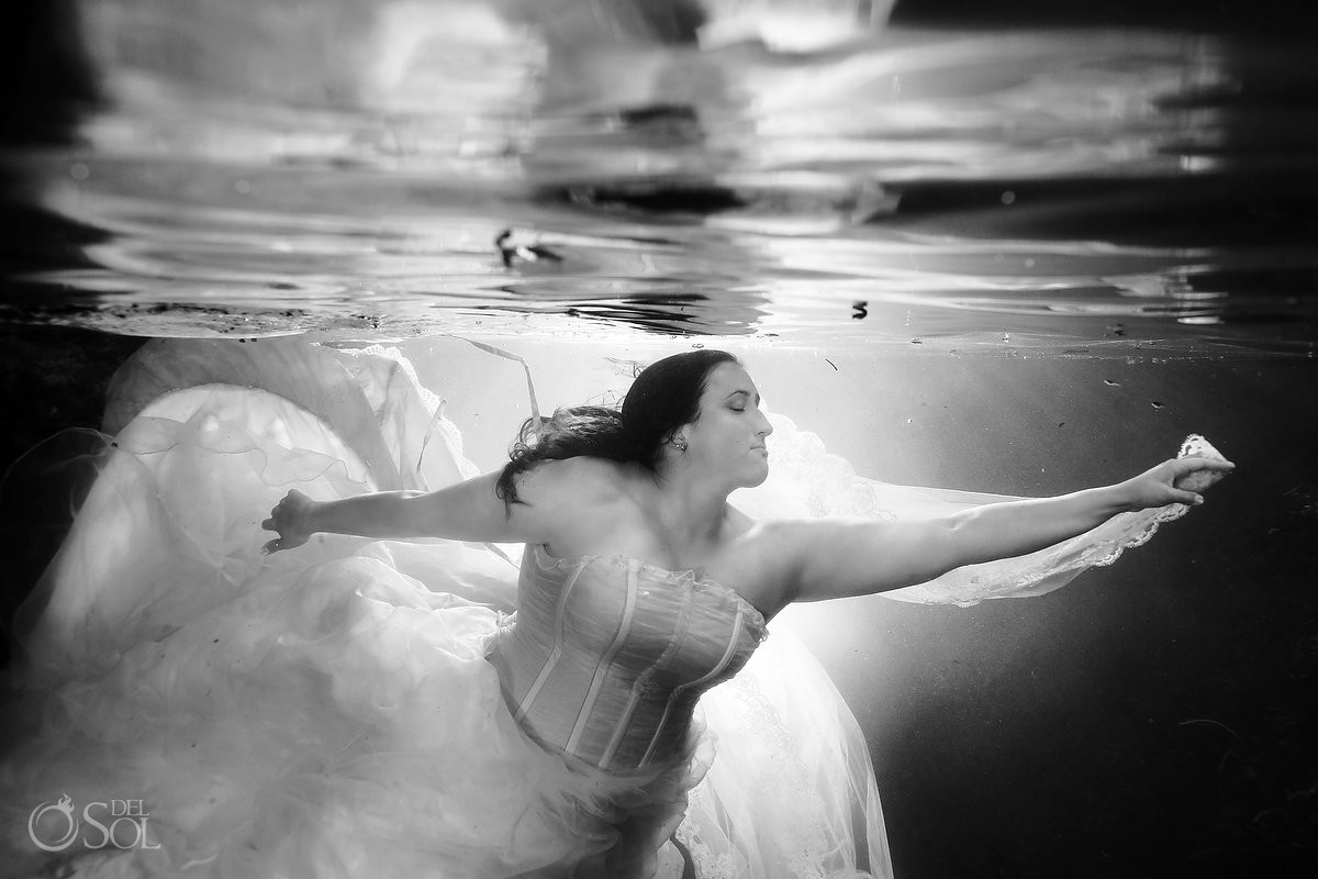 Underwater trash the dress bride in a cenote in the Riviera Maya, Mexico