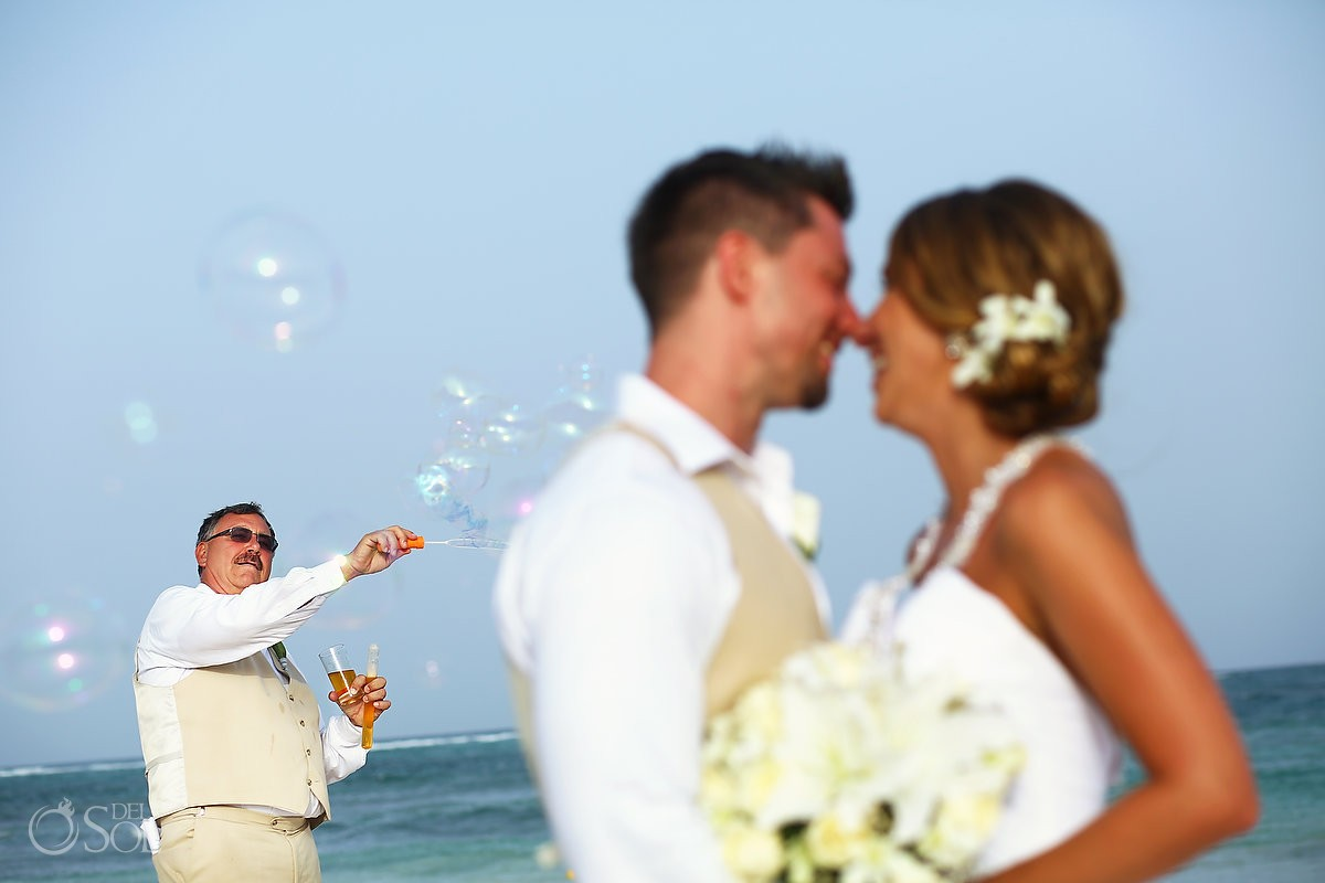 father blows bubbles in the background as bride and groom kiss at dreams tulum wedding