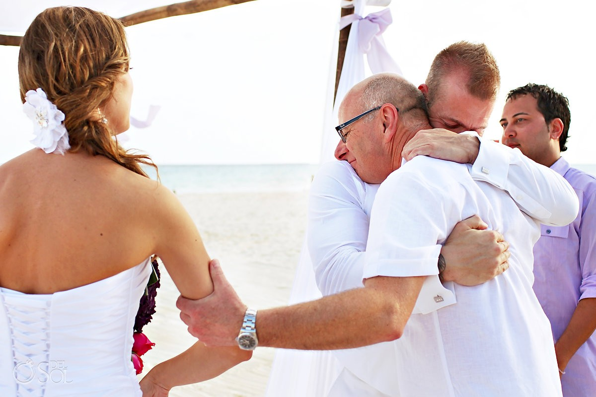 father hugs groom as he gives away his daughter for a beach wedding in mexico