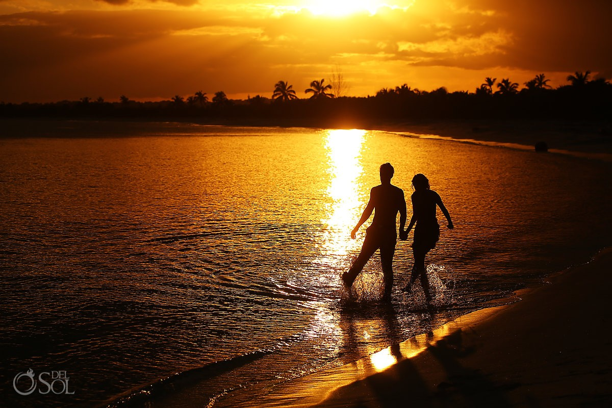 Couple at sunset walking on the beach at blue venado