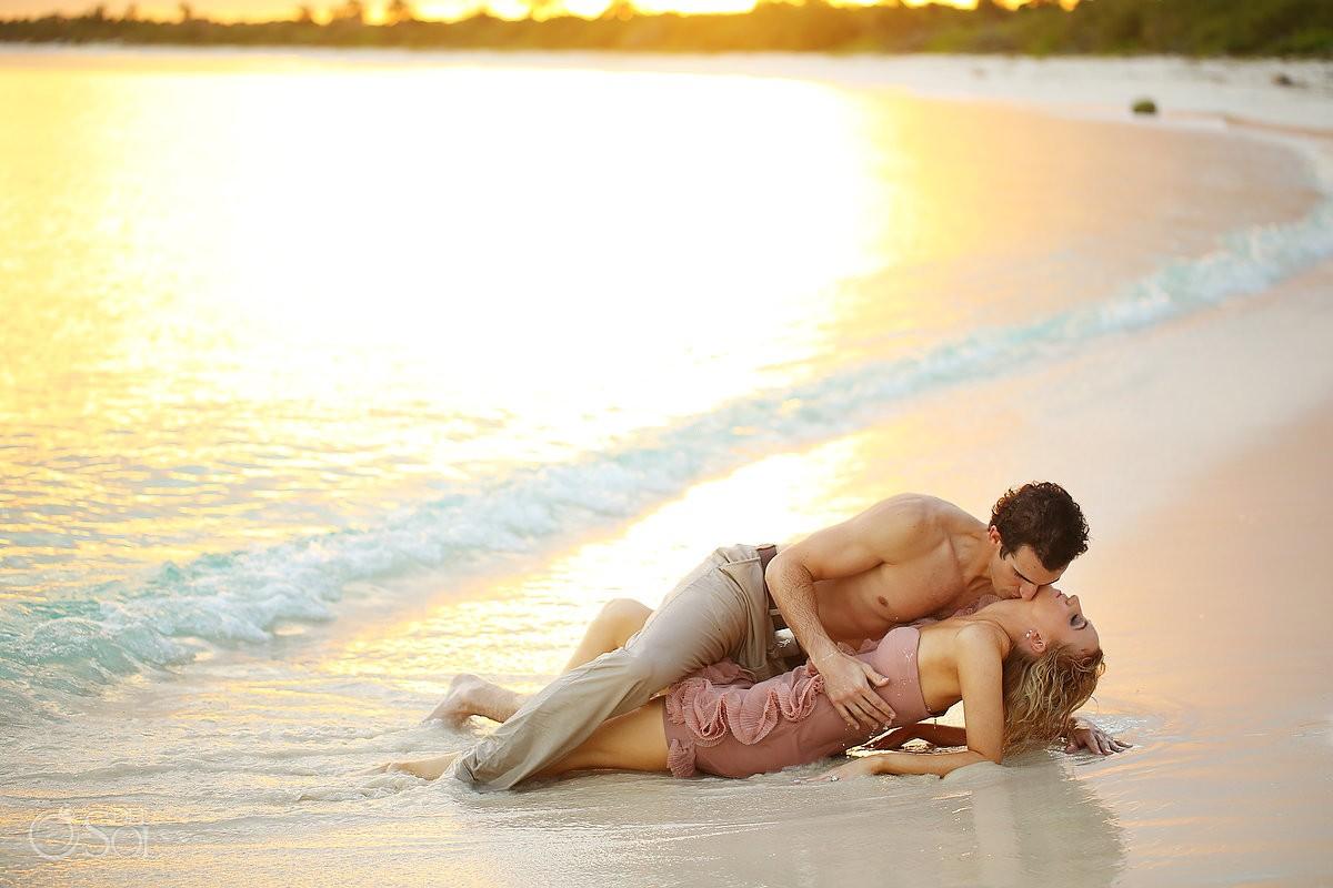 riviera maya engagement young lovers kiss on the sand at Blue Venado Beach