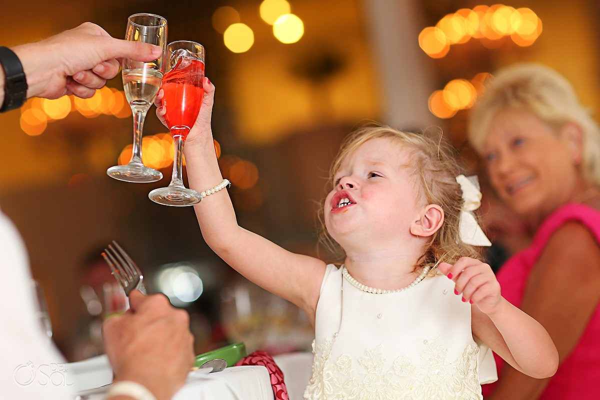 Small flowergirl toasting during a wedding reception