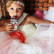 small flowergirl drinking hershey's milk at a wedding ceremony