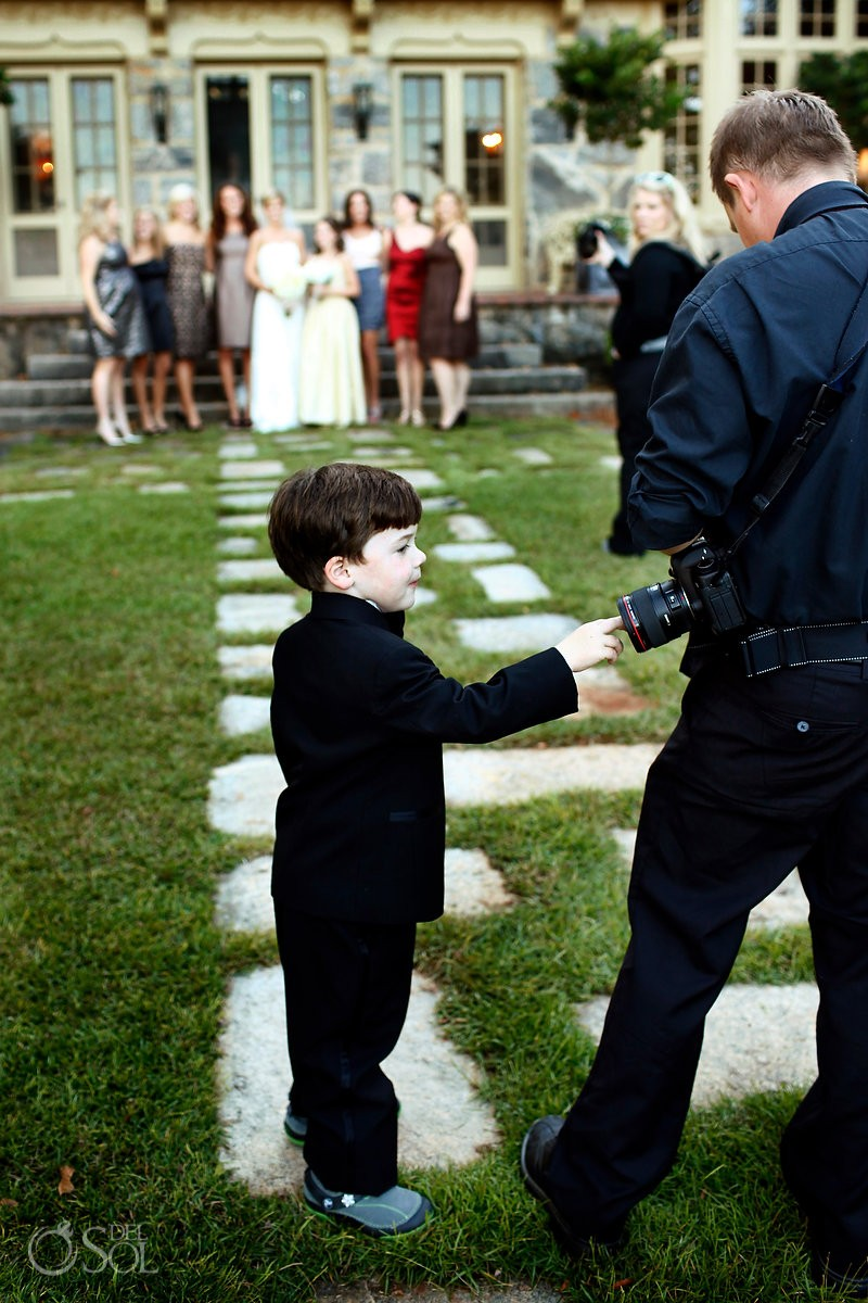 child touches the lens of a wedding photographer
