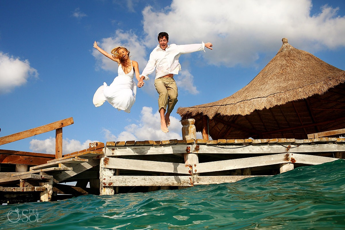 bride and groom leaping into the caribbean ocean from a dock in riviera maya mexico trash the dress