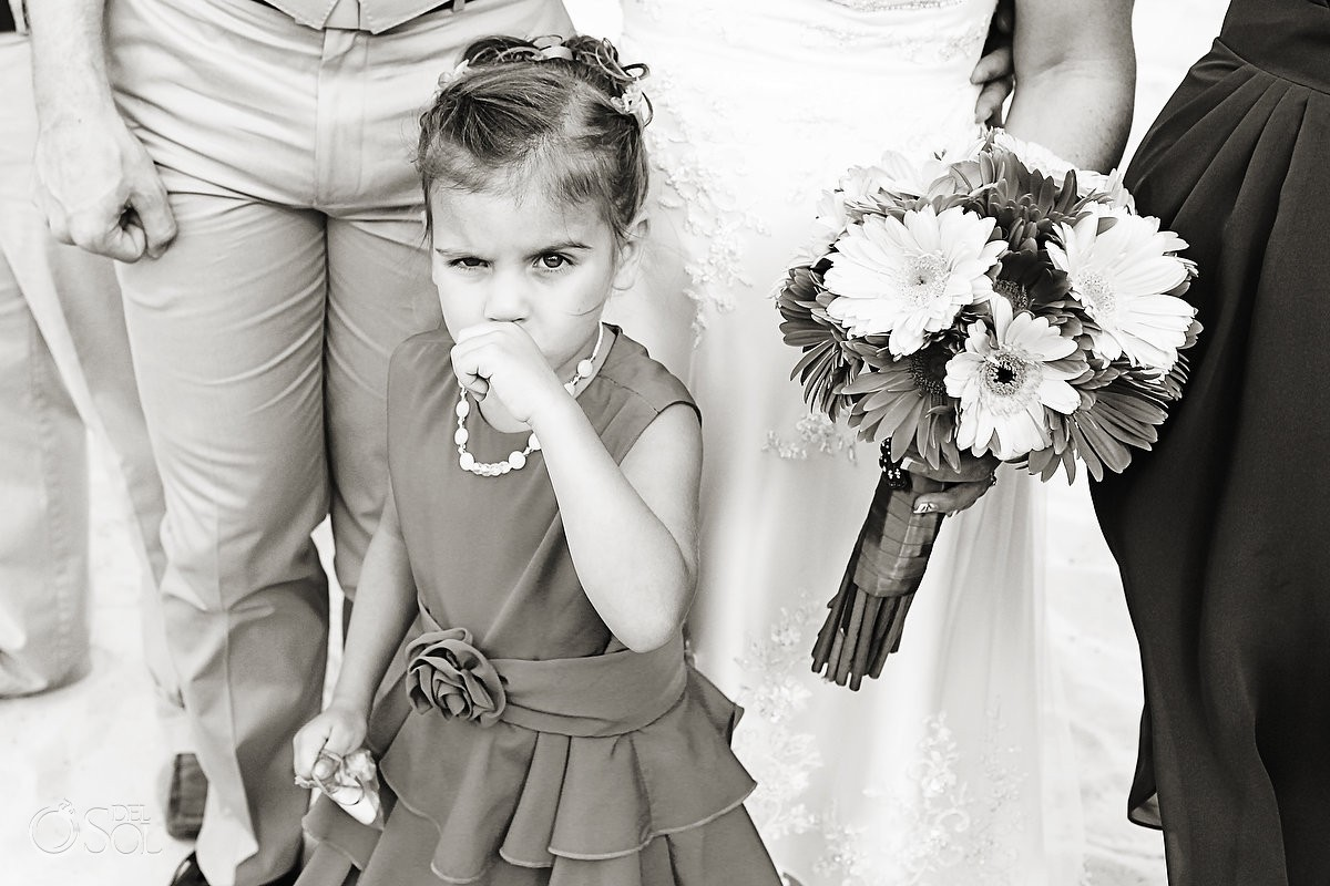 Small flowergirl pouting during a wedding ceremony