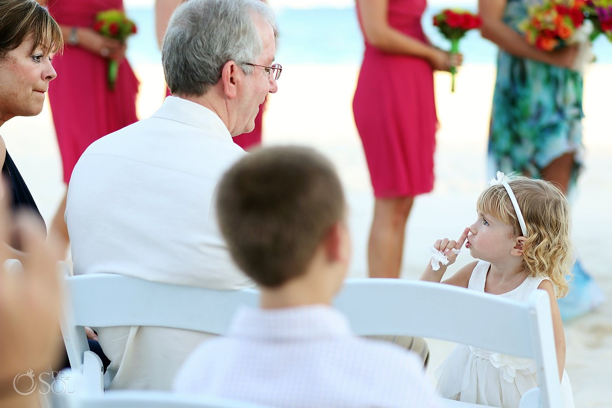 small flowergirl hushes wedding guest making noise