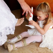 Laura, the brides daughter and flower-girl with leg braces helps her mother put on bride shoes at a wedding