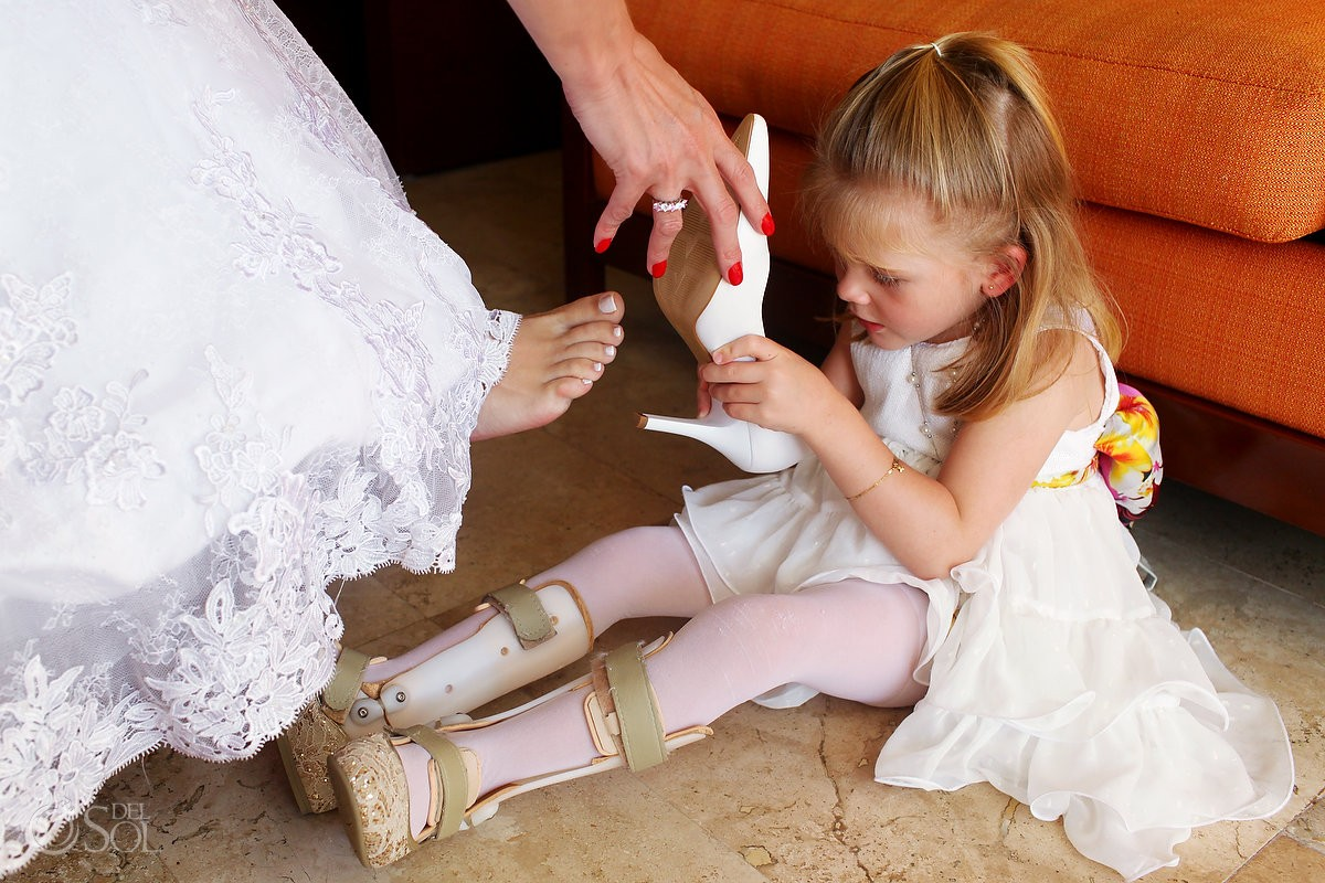 small flowergirl with leg braces helps mother put on bride shoes at a wedding