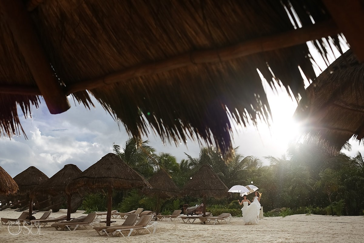 bride walks on the rainy beach for destination wedding at secrets maroma hotel
