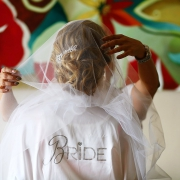 "bride wearing a robe with sequin letters spelling ""Bride"""