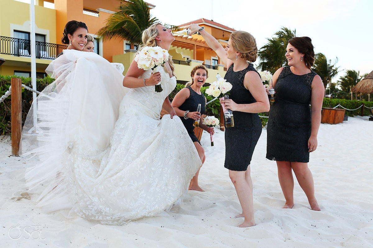 Bride drinking a Corona Beer during a beach wedding portrait session with bridesmaids at Ocean Coral Turquesa Hotel