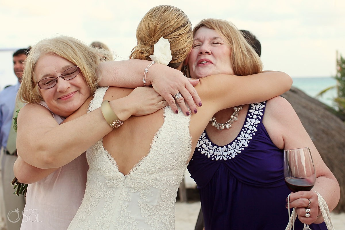 bride hugs mothers at her beach destination wedding in mexico