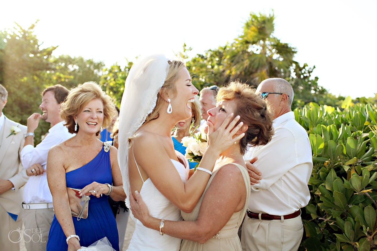 bride and mother embrace at beach wedding in mexico