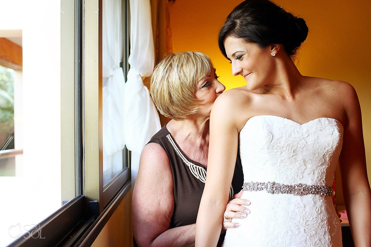 Mother kisses bride getting ready for a destination wedding in mexico