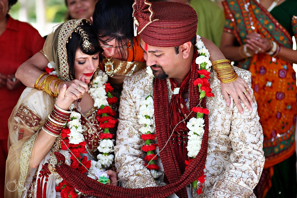 hindu bride and groom embraced by mother