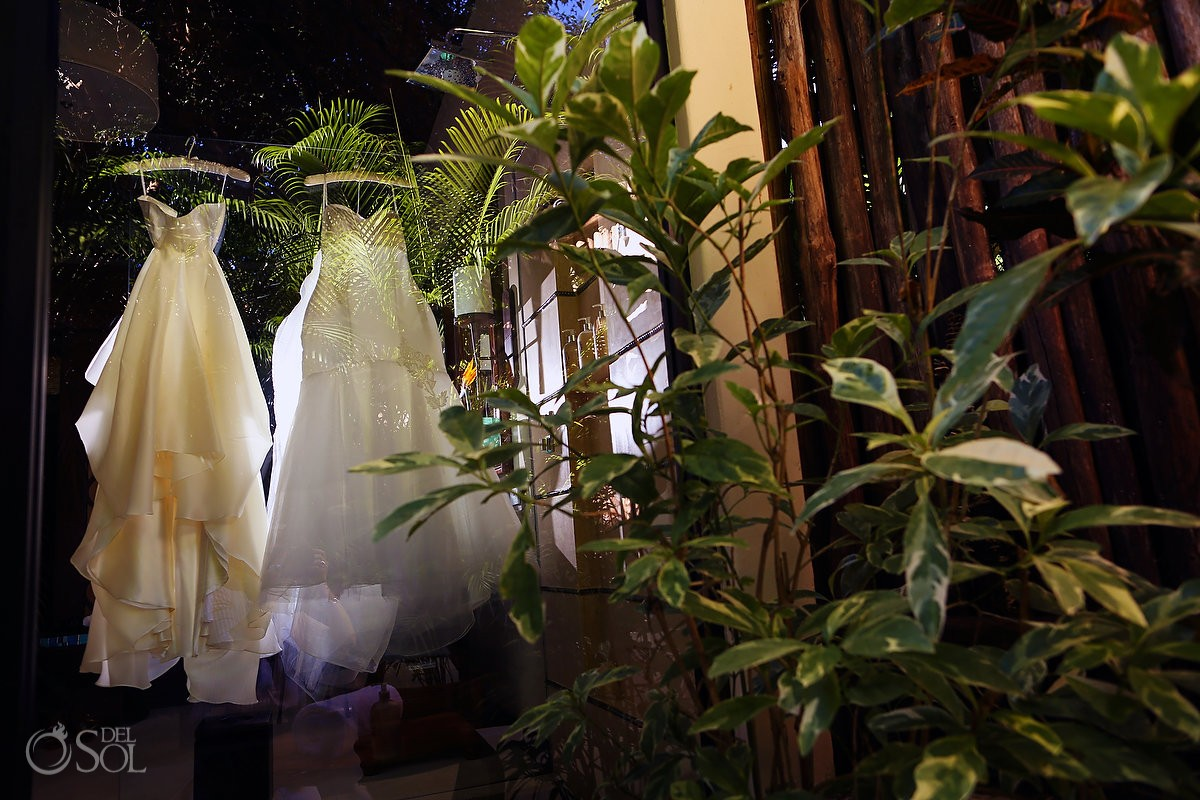 two wedding dresses hanging jungle leaves reflection Viceroy Riviera Maya