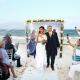 Guests shake maracas as bride and groom exit beach wedding at belmond maroma resort