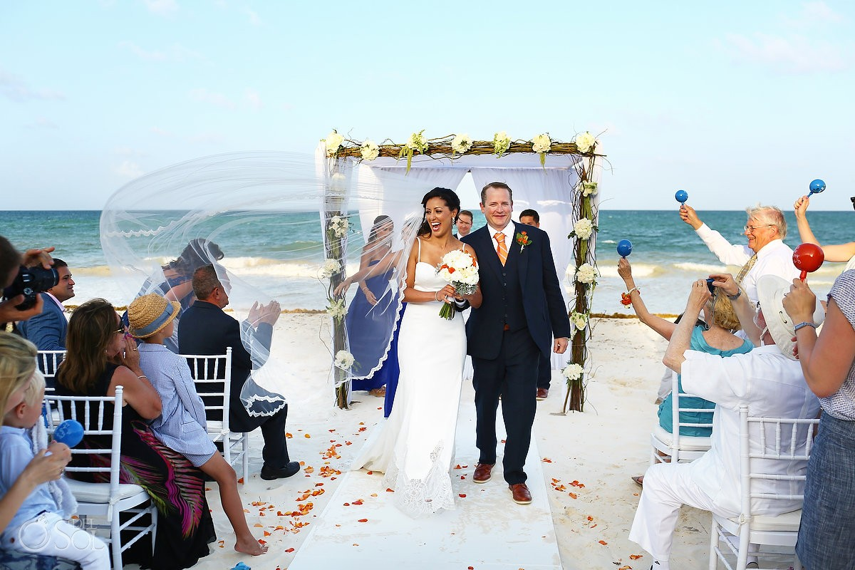 Guests shake maracas as bride and groom exit beach wedding at belmond maroma resort