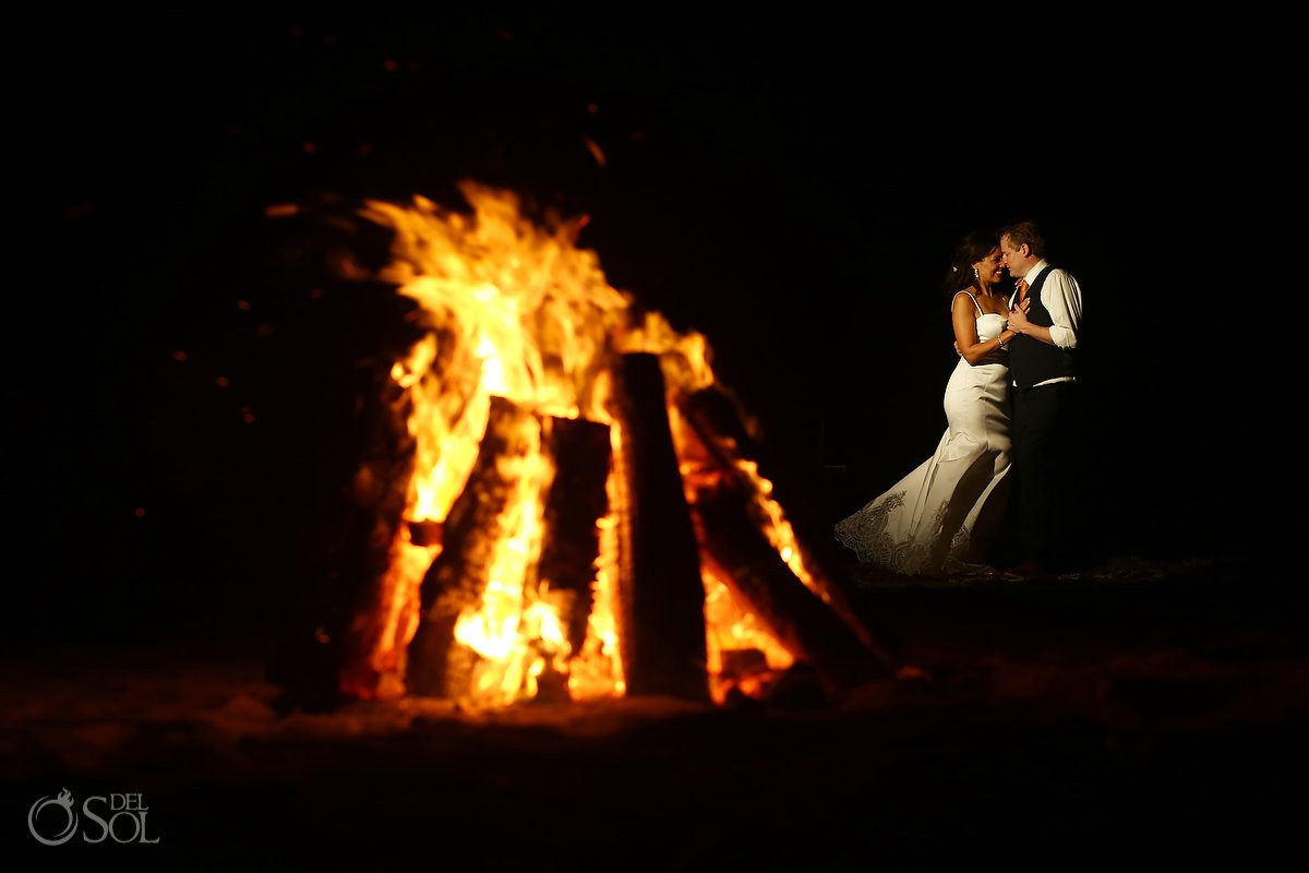 Destination wedding photo of bride and groom at campfire on the beach belmone maroma resort