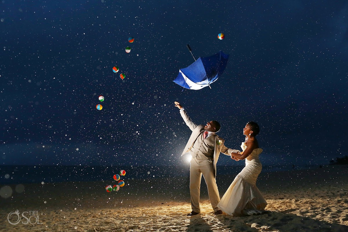 destination beach wedding photo with bride and groom throwing umbrella