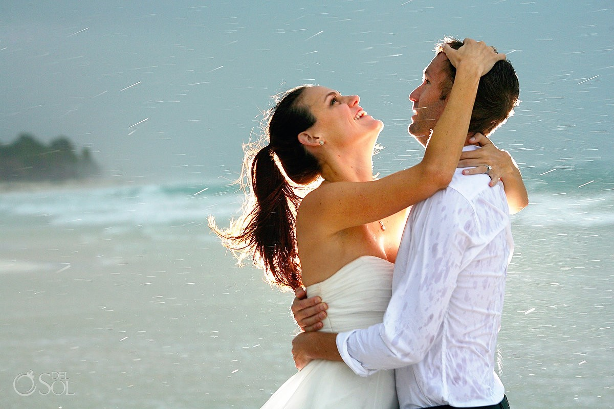 bride and groom in the rain in tulum beach mexico