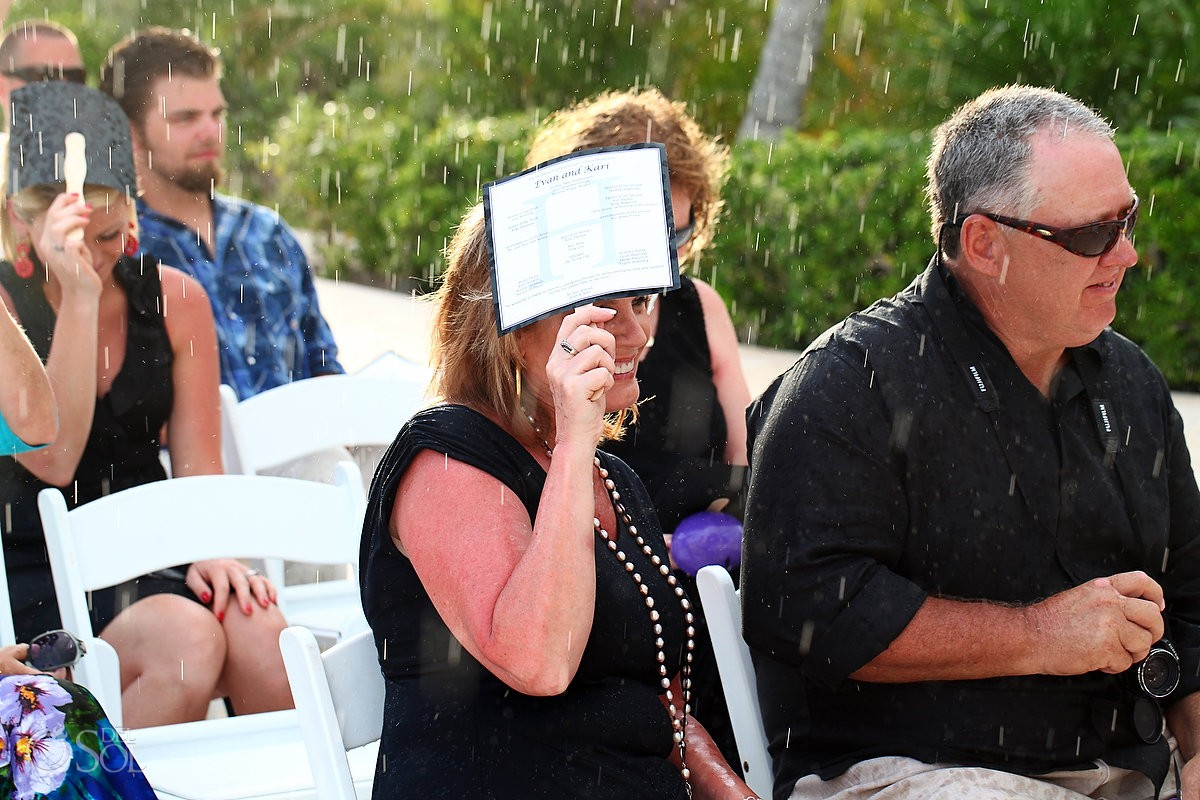 destination wedding guests wait in the rain at secrets maroma hotel mexico