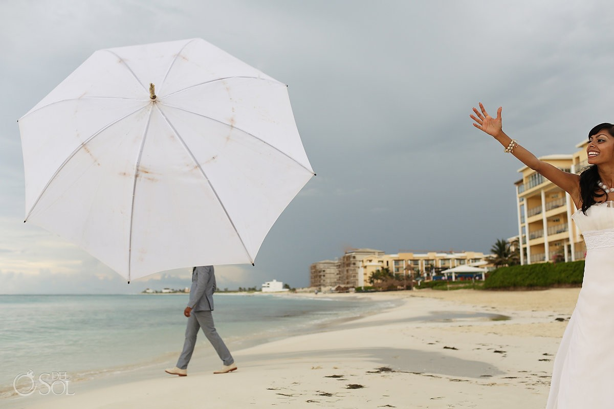 destination wedding photo in the rain with bride throwing umbrella at groom at now jade hotel