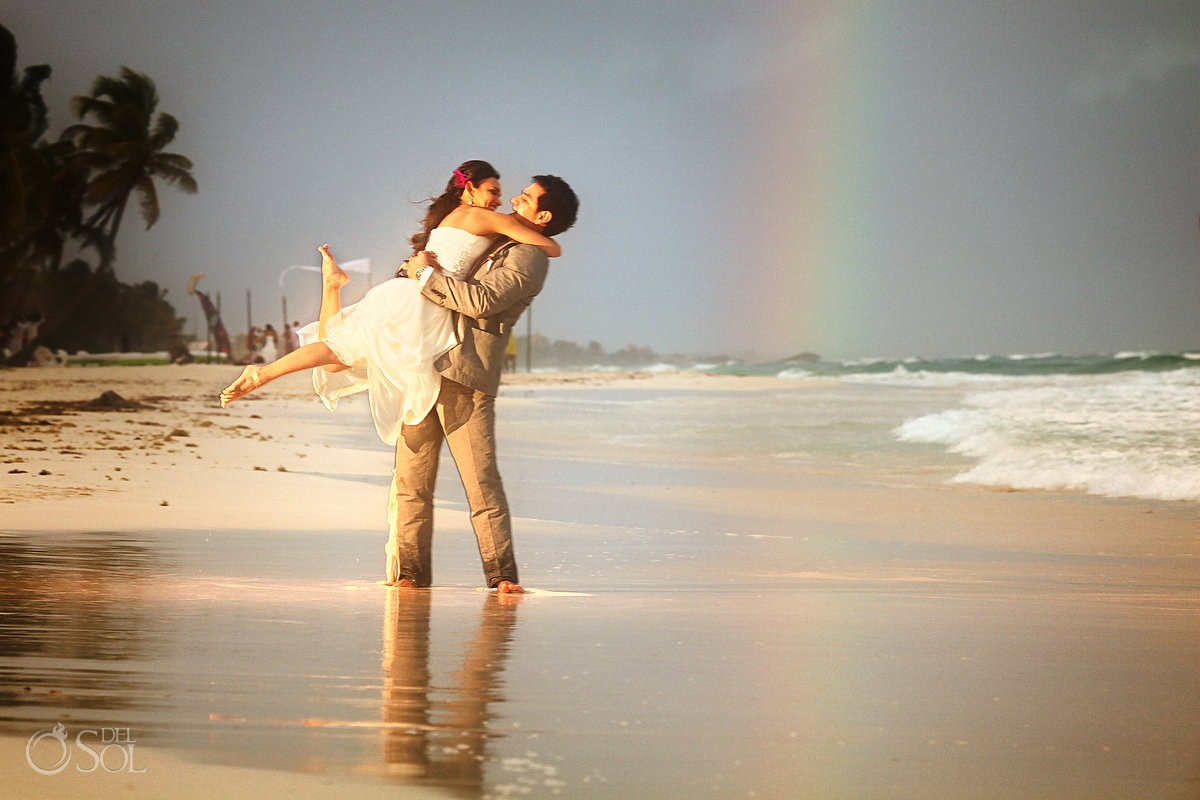destination wedding photo of bride and groom under a rainbow in the Tulum beach