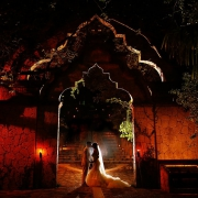 Architectural bride and groom night time wedding portrait inside the arch of Xcaret Park, Riviera Maya, Mexico