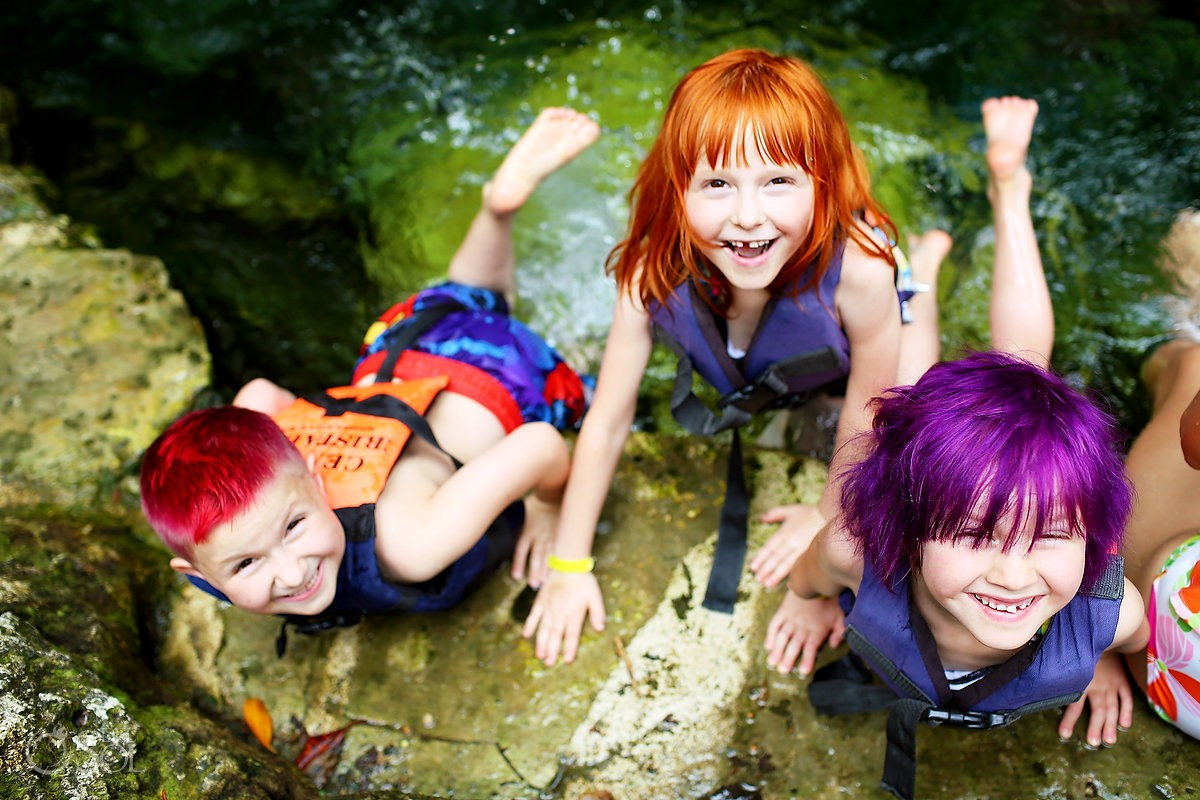 children play in the cenote with the family in mexico